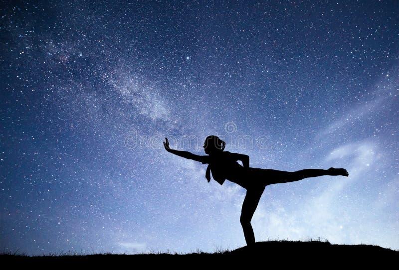 Manière laiteuse avec la silhouette d'un yoga de pratique de femme debout sur la montagne Beau paysage avec la fille méditante image libre de droits