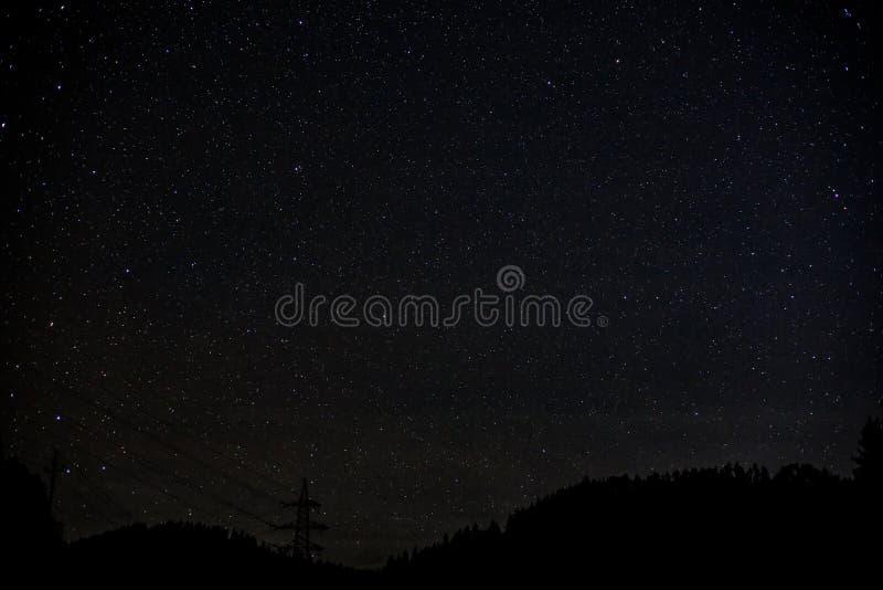 Manière laiteuse de ciel nocturne avec milliard d'étoiles et de silhouette d'arbre et de ligne électrique photos stock
