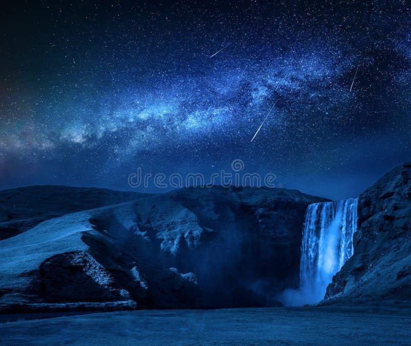 Manière laiteuse et étoiles filantes au-dessus de cascade de Skogafoss en Islande images stock