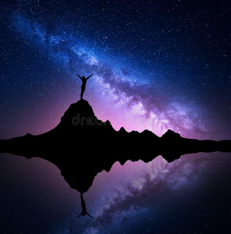 Manière laiteuse et silhouette d'une femme debout sur la montagne photos libres de droits
