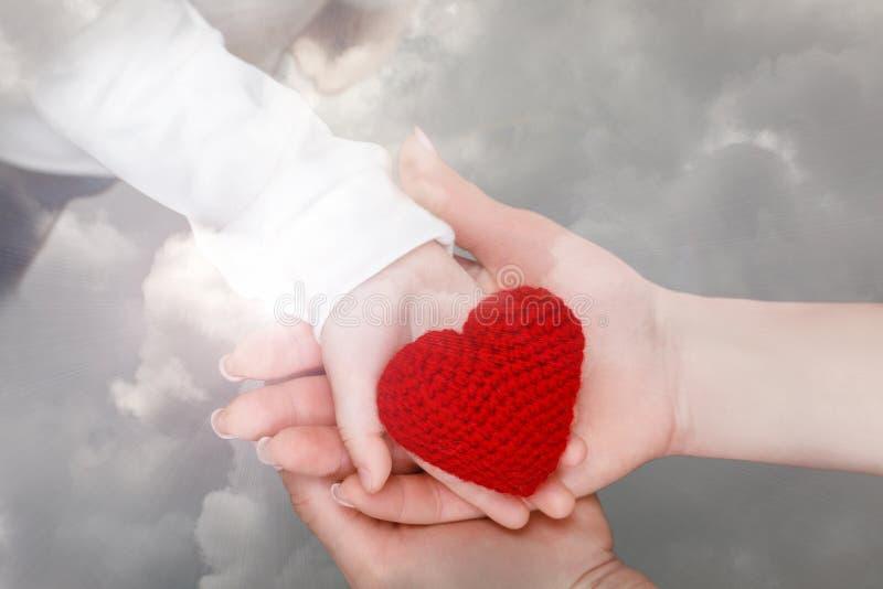 Mani adulte femminili con la palma del bambino che tiene un cuore tricottato fotografia stock libera da diritti