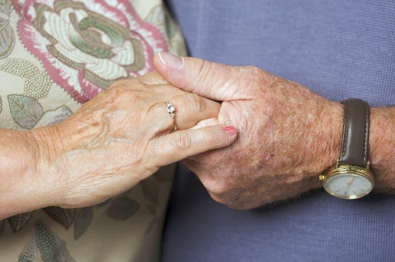 Mani adulte maggiori della holding delle coppie fotografia stock