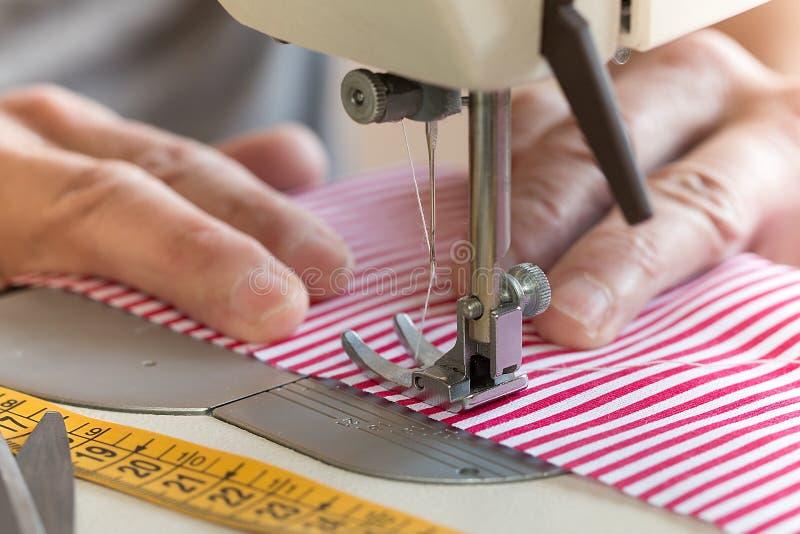 Mani alla macchina per cucire che tiene un certo tessuto fotografie stock libere da diritti