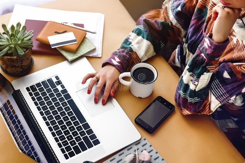 Mani alla moda dei pantaloni a vita bassa della ragazza sul computer portatile che cerca e che scrive, freel immagine stock