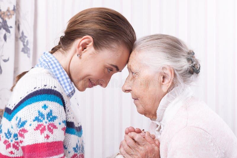Mani amiche, anziano di concetto di assistenza agli'anziani e badante tenentesi per mano a casa immagini stock libere da diritti
