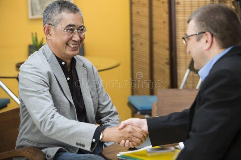 Mani asiatiche di Shake dell'uomo d'affari fotografie stock
