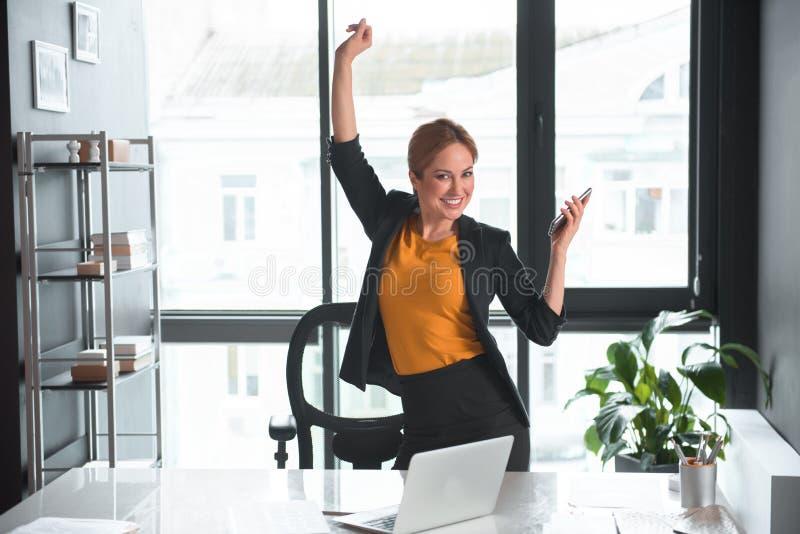 Mani in aumento della donna di affari felice su con il telefono fotografia stock libera da diritti