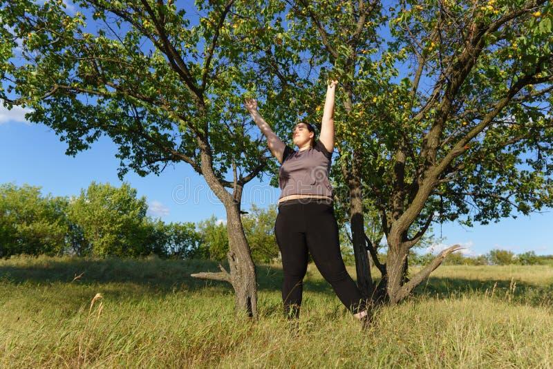 Mani in aumento della donna di peso eccessivo verso il cielo fotografia stock libera da diritti
