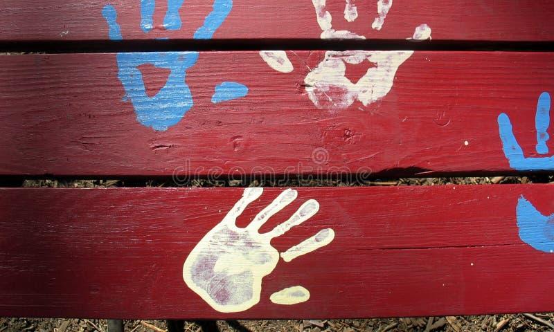 Mani blu e bianche su colore rosso immagini stock