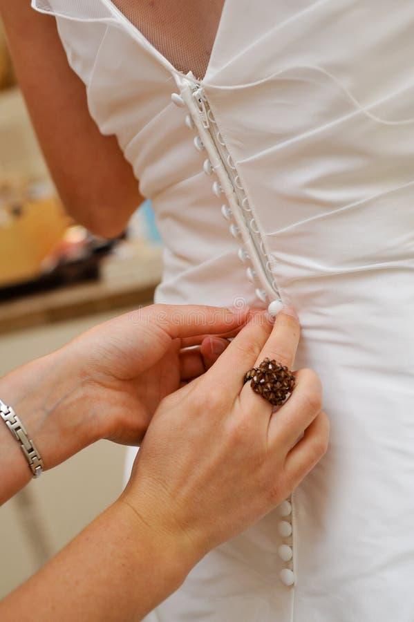 Mani che abbottonano il vestito da cerimonia nuziale fotografia stock