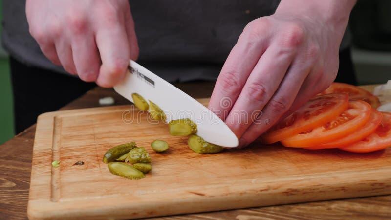 Mani che affettano cetriolo e pomodoro sul tagliere fotografie stock