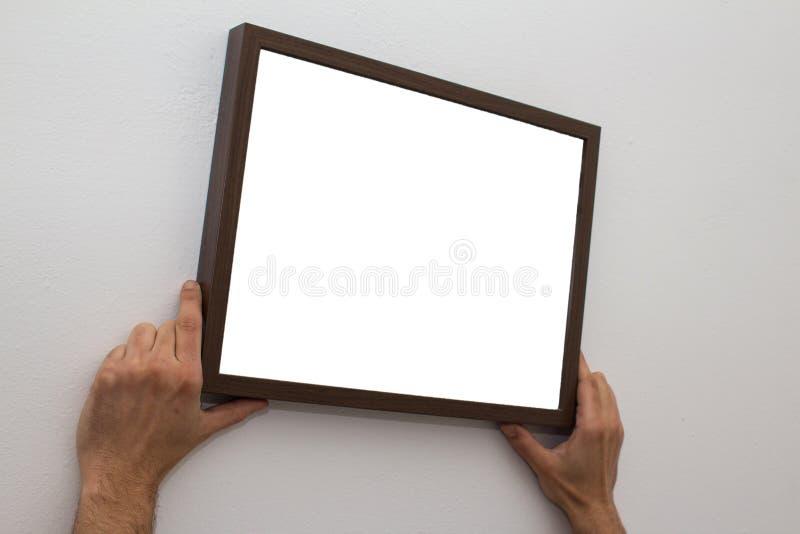 Mani che appendono la cornice in bianco sulla parete immagine stock