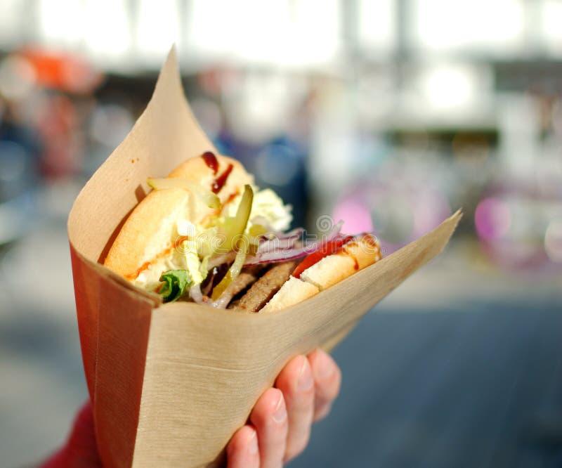 Mani che giudicano avvolte in hamburger di carta sul fondo della città immagini stock
