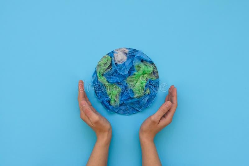 Mani che giudicano pianeta Terra fatto dai pacchetti eliminabili di plastica su fondo blu Conservi il mondo, creativo, ambiente immagini stock