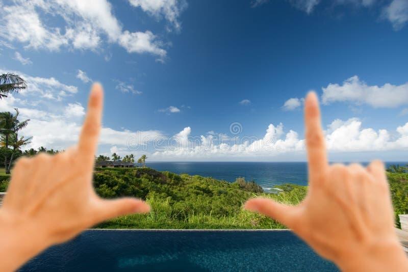 Mani che incorniciano vista di oceano hawaiana strabiliante fotografia stock libera da diritti