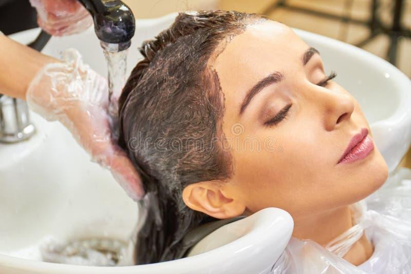 Mani che lavano fuori dalla tintura per capelli fotografie stock libere da diritti