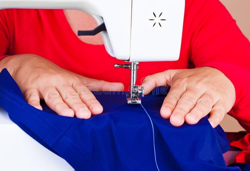 Mani che lavorano ad una macchina per cucire fotografia stock