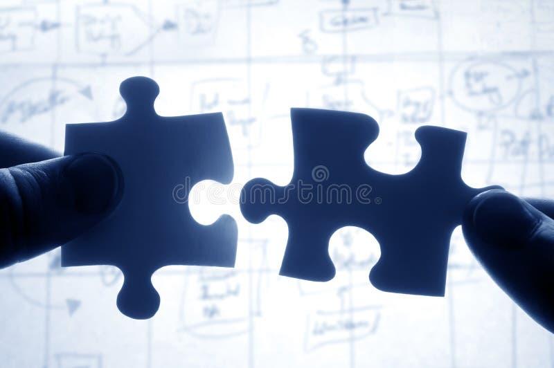 Mani che provano a misura puzzle due fotografia stock libera da diritti