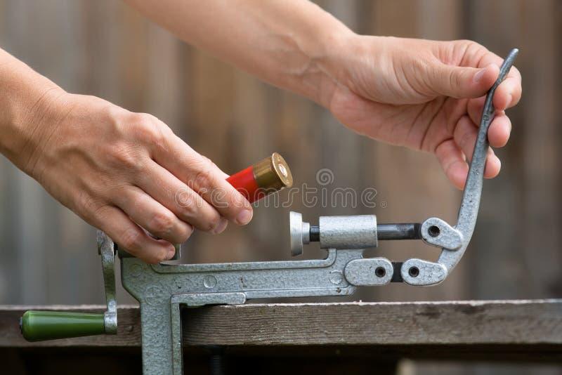 Mani che ricaricano cartuccia dal reloader della cartuccia per fucili a canna liscia fotografia stock