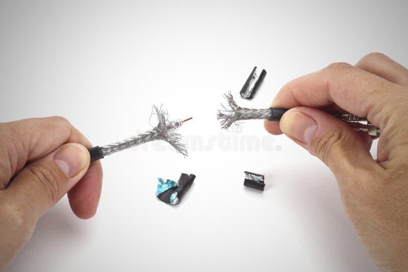 Mani che rimuovono schermo dal singolo connettore di cavo coassiale professionale immagini stock