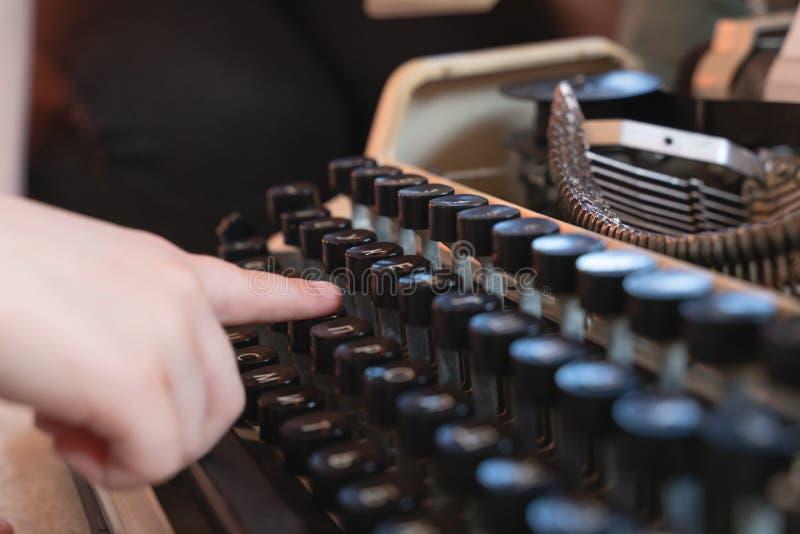 Mani che scrivono su una vecchia macchina da scrivere stile retro tastiera e fonte fotografia stock libera da diritti