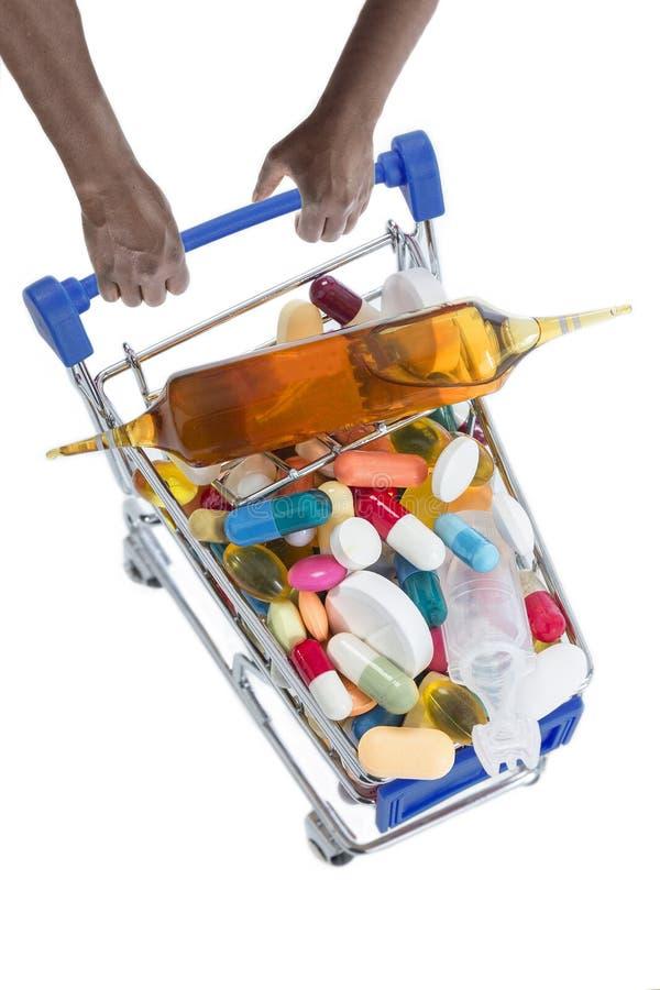 Mani che spingono i carrelli del supermercato riempiti di pillole fotografia stock