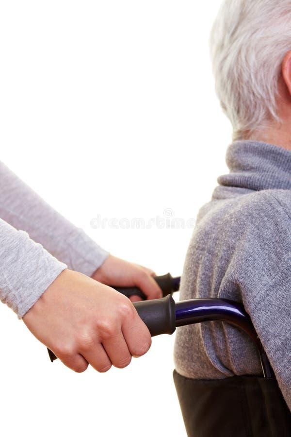 Mani che spingono sedia a rotelle immagini stock