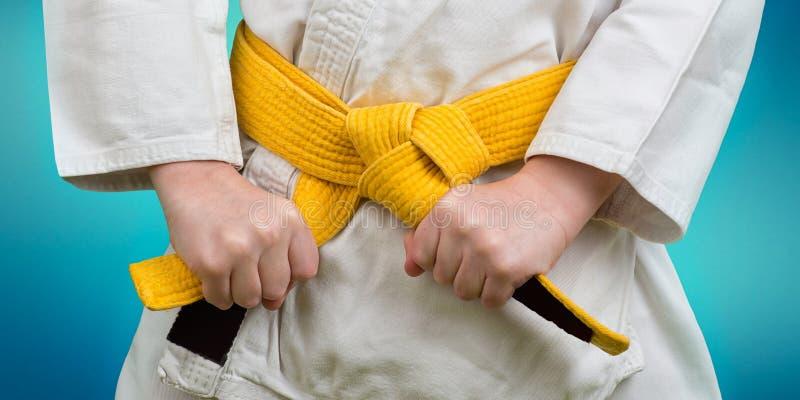 Mani che stringono cinghia gialla su un adolescente vestita in kimono per le arti marziali immagini stock