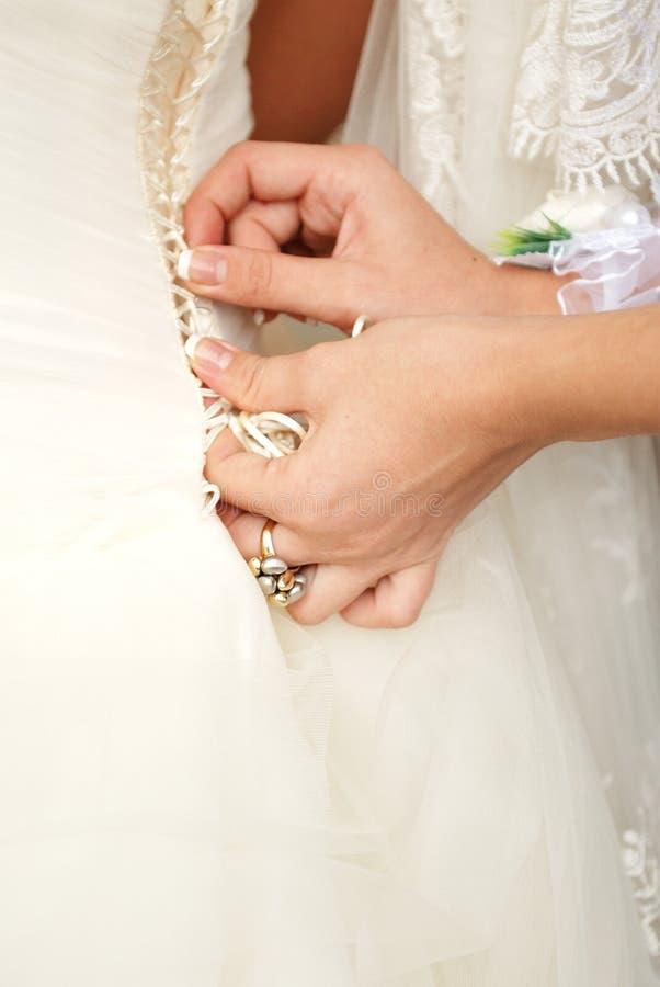 Mani che stringono un corsetto alla sposa immagine stock