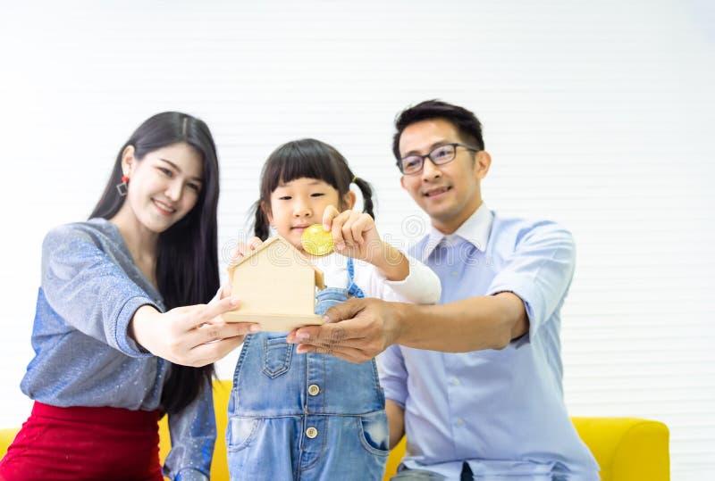 Mani che tengono banca piggy Soldi di risparmio della famiglia alla banca domestica di legno Bambina graziosa e famiglia che mett fotografia stock