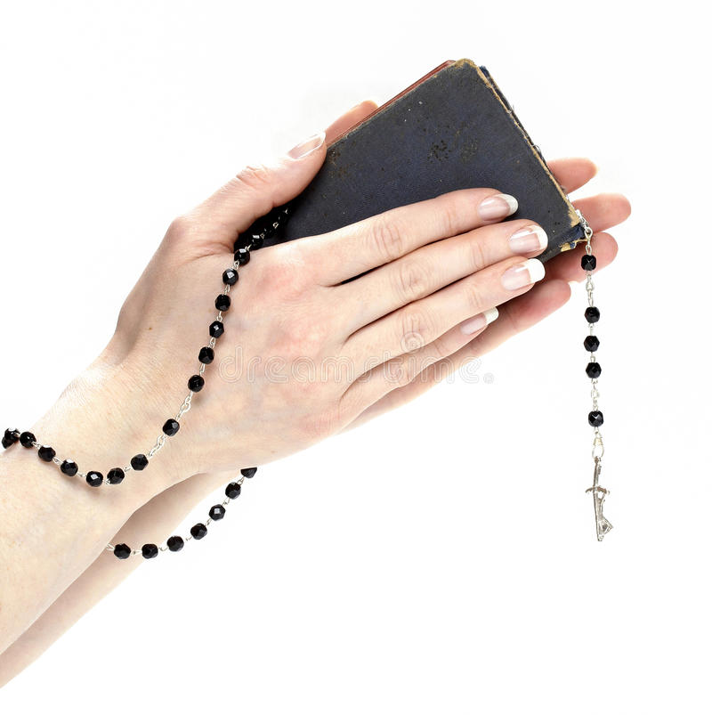 mani che tengono bibbia e che pregano con un rosario immagini stock libere da diritti