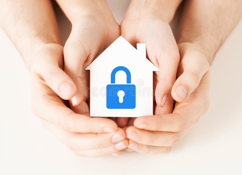 Mani che tengono casa di carta con la serratura immagine stock libera da diritti