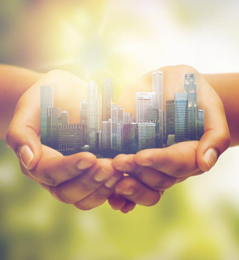 Mani che tengono città sopra sfondo naturale verde fotografia stock libera da diritti