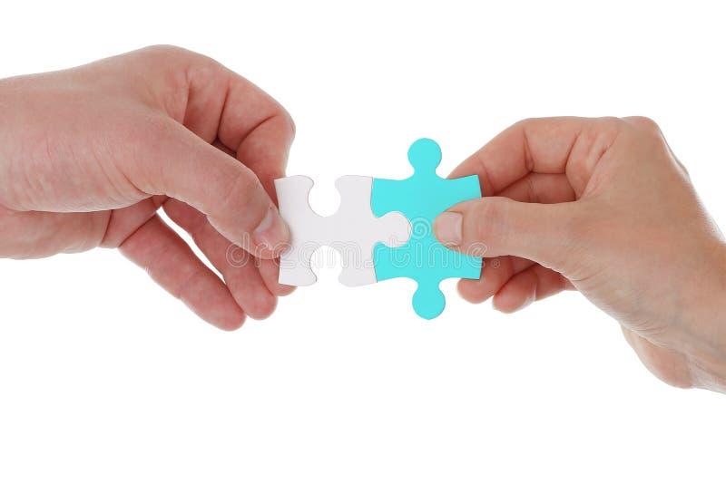 Mani che tengono e che uniscono due pezzi di puzzle isolati insieme Concetto di cooperazione e di corrispondenza di associazione  immagini stock libere da diritti