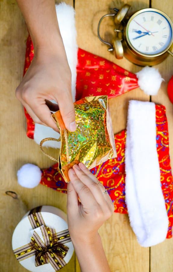 Mani che tengono giftbag sopra lo scrittorio con il Natale fotografia stock libera da diritti