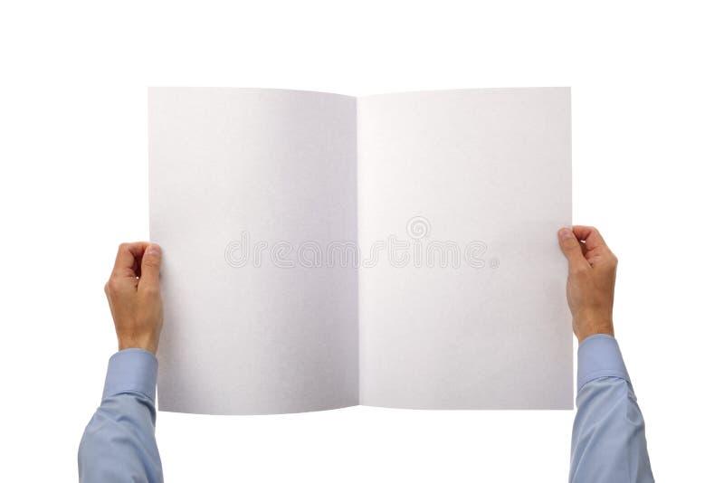Mani che tengono giornale in bianco immagine stock