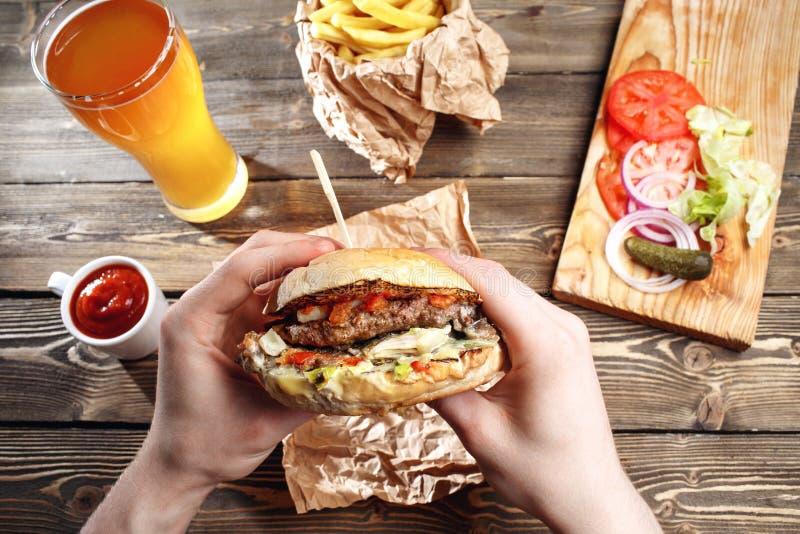 Mani che tengono gli hamburger deliziosi freschi con le patate fritte, la salsa e la birra sulla vista di legno del piano d'appog immagine stock
