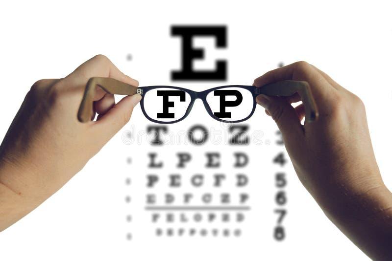 Mani che tengono gli occhiali con il grafico di prova visivo Concetto dell'ottico di vista fotografia stock libera da diritti