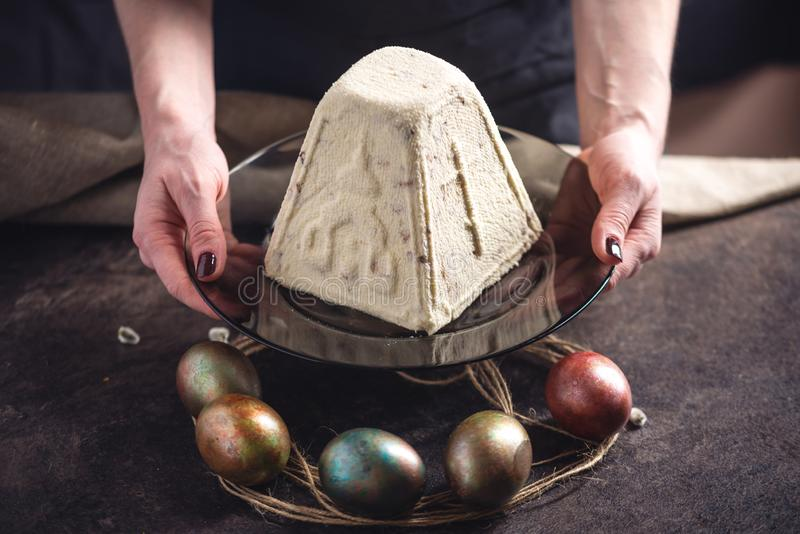 Mani che tengono i dessert tradizionali e le uova variopinte nello stile rustico su un fondo scuro Pasqua felice immagini stock libere da diritti