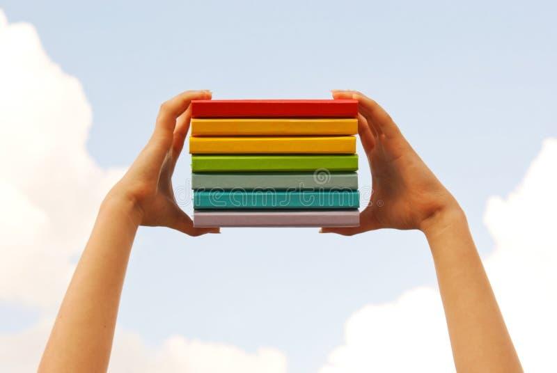 Mani che tengono i libri duri variopinti del coperchio fotografia stock