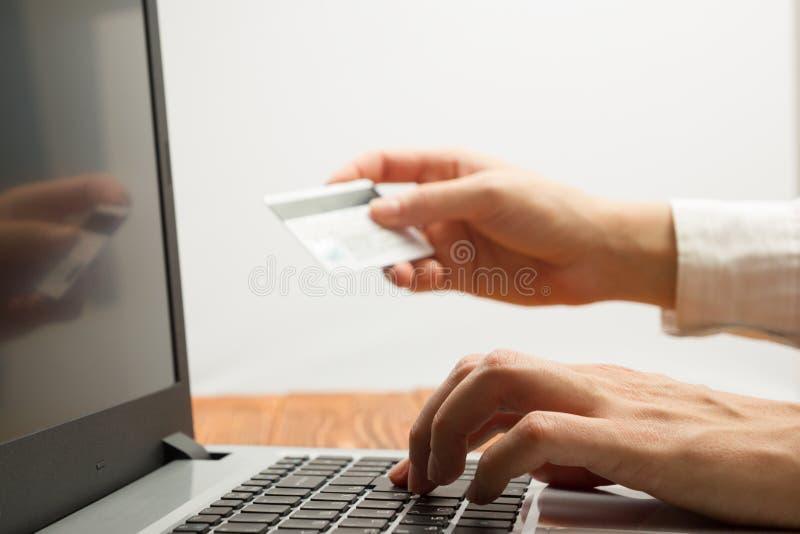 Mani che tengono i numeri di battitura a macchina della carta di credito sul pc della compressa che rende a pagamento online a ca fotografia stock