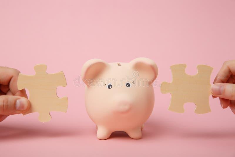 Mani che tengono i pezzi di legno del puzzle vicino alla banca dei soldi di porcellino sul fondo rosa pastello della parete Soldi fotografie stock libere da diritti