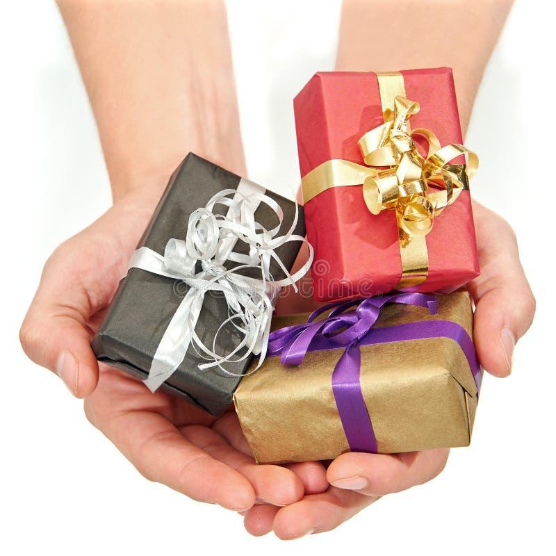 Mani che tengono i piccoli regali di Natale immagini stock