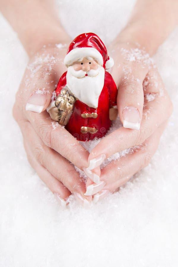 Mani che tengono il Babbo Natale - concetto per natale con i chiodi fotografia stock