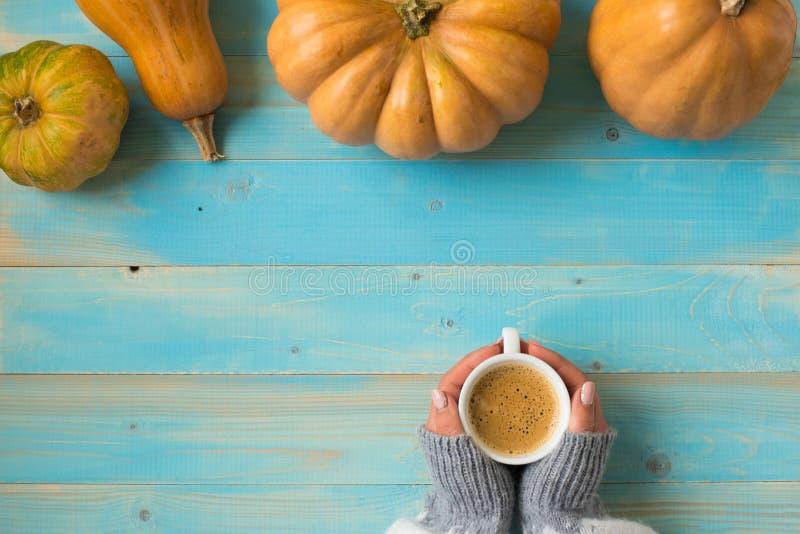 Mani che tengono il caffè della tazza su fondo blu fotografia stock