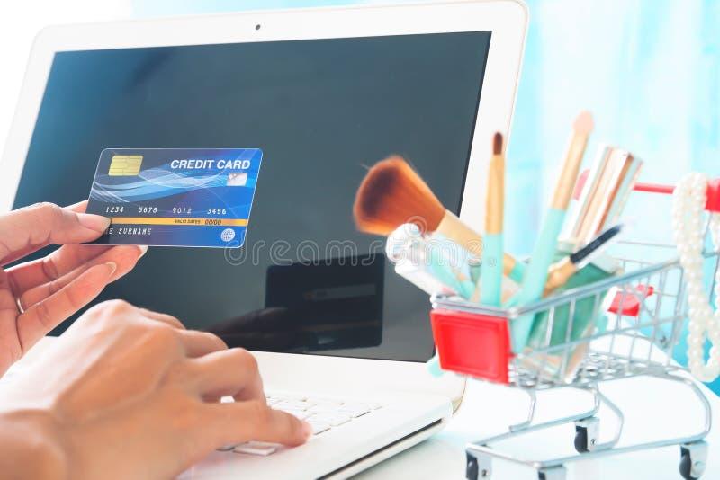 Mani che tengono la carta di credito e che per mezzo del computer portatile Acquisto di bellezza, E-pagamento o attività bancarie immagine stock libera da diritti