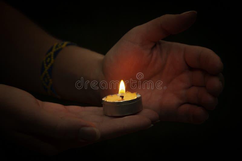 Mani che tengono la luce della candela immagine stock libera da diritti