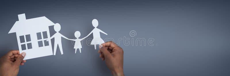 Mani che tengono le figure di carta contro il fondo blu come concetto di assicurazione della famiglia e della casa immagini stock