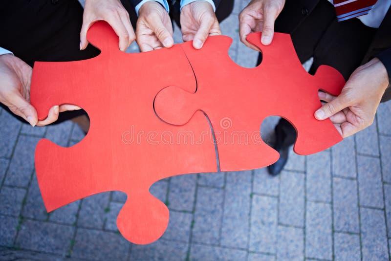 Mani che tengono le parti di puzzle di puzzle fotografia stock