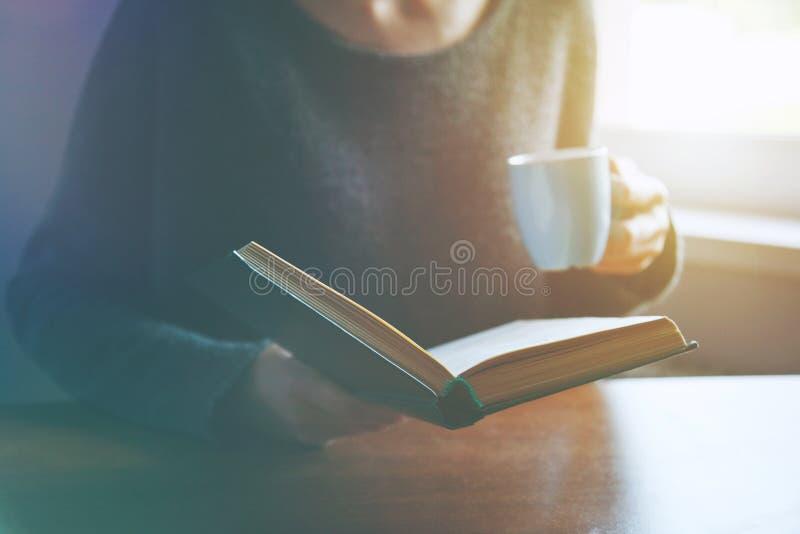 Mani che tengono libro e che leggono con il caffè fotografia stock libera da diritti